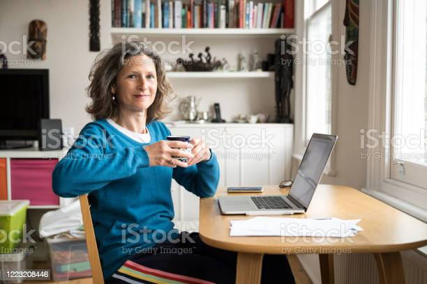 Caucasian woman in casual clothing sitting at her desk at home