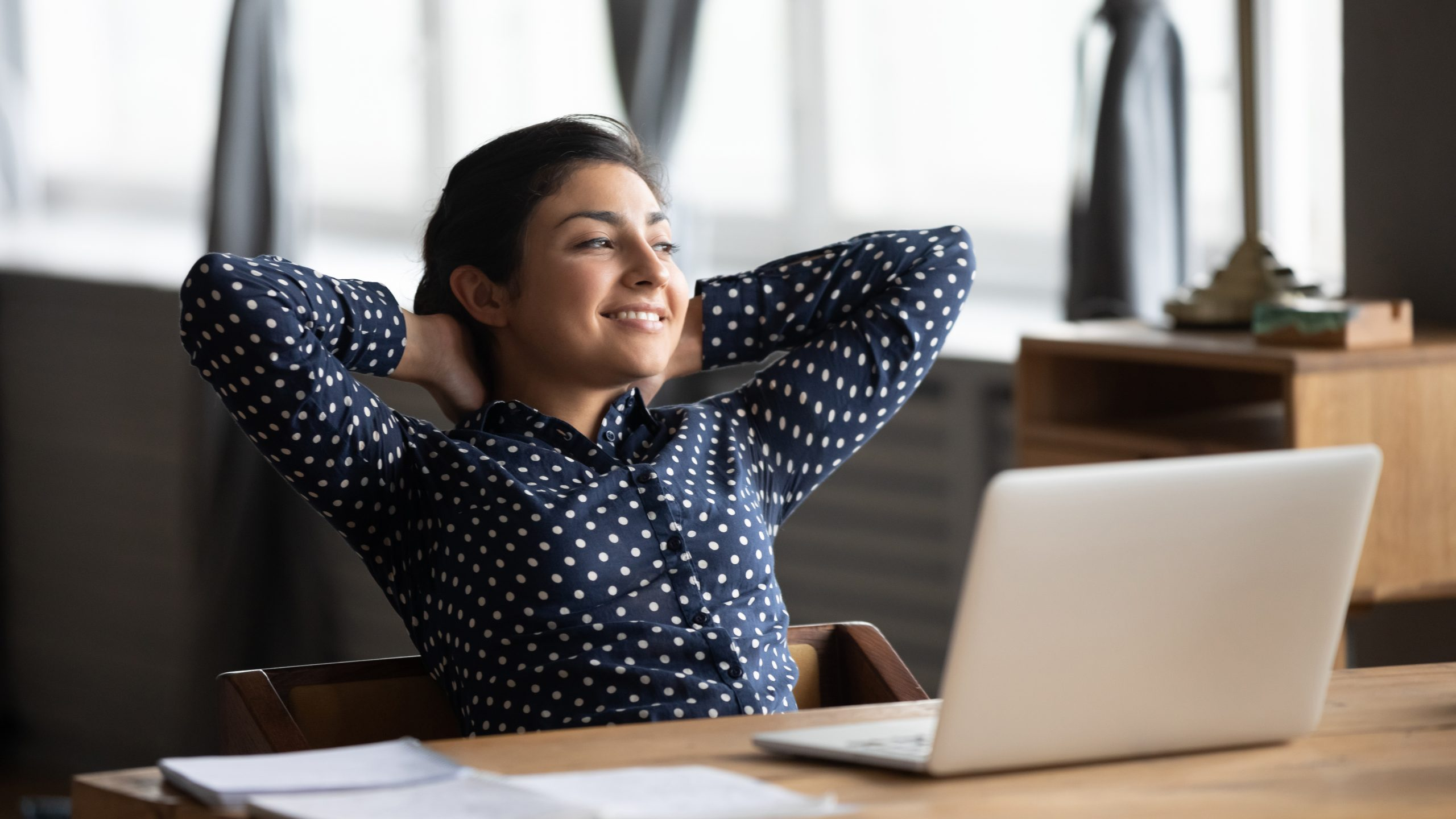 Carefree indian employee resting after productive workday leaned on office chair puts hands behind head look out the window feels well by career advance and achievement, dreams about vacation concept